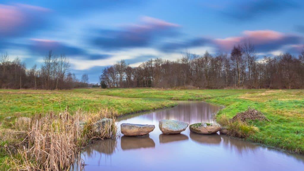 Hunebed stenen over een kleine rivier in Drenthe