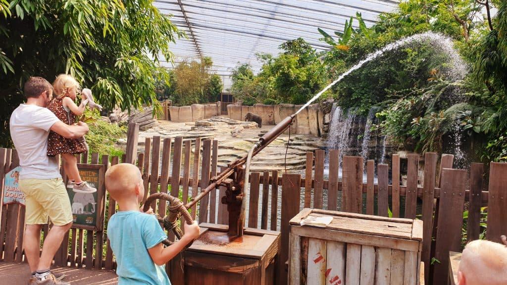 Kind speelt met waterspuit bij de olifanten in Jungola