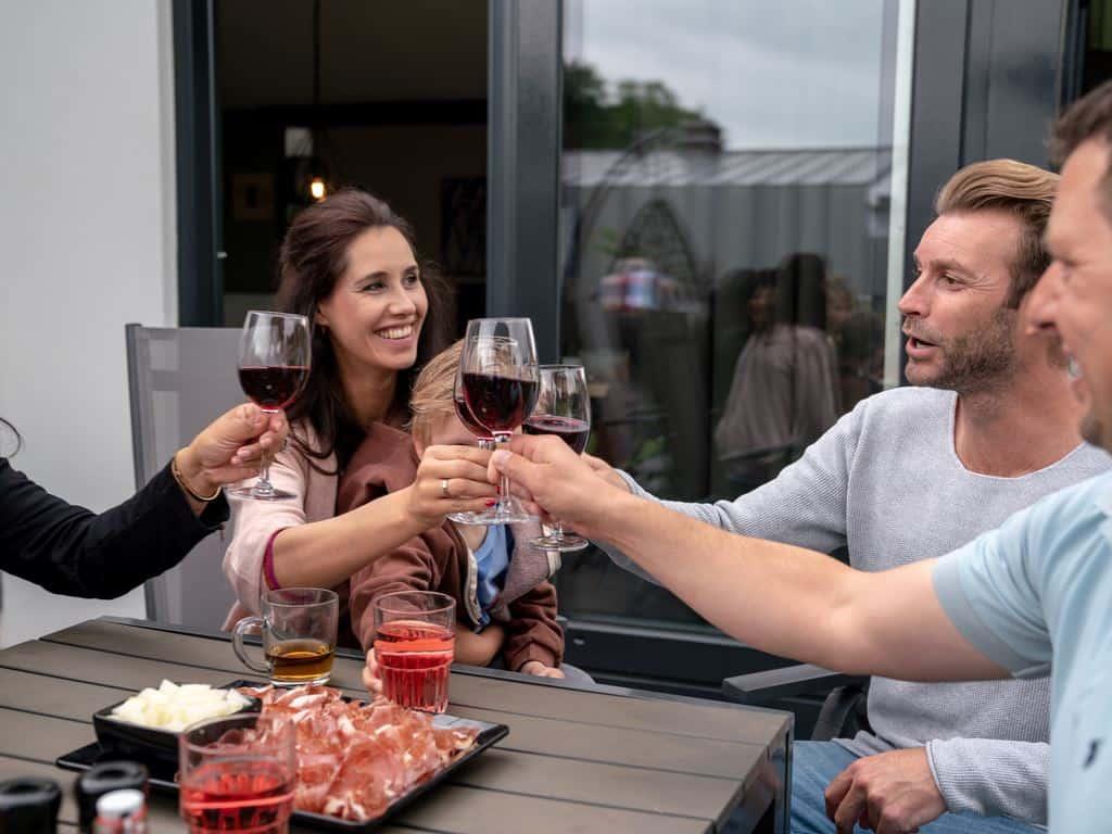 Vrienden samen aan het wijn drinken bij een vakantiehuisje