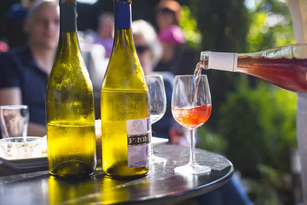 Glas wijn wordt ingeschonken met meerdere glazen wijn op tafel