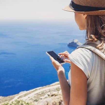 Vrouw met telefoon bij een klif met uitzicht op zee