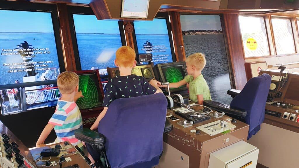 Drie kinderen aan het spelen op een simulator van een veerboot in het Abraham Fock museum