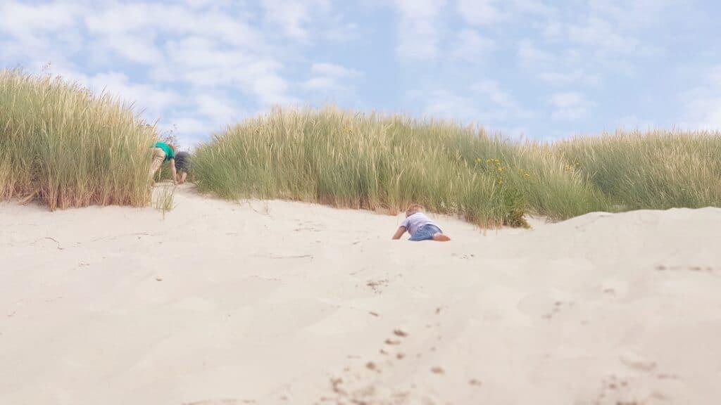 Kinderen aan het spelen in de duinen op het strand van Ameland